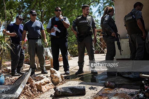 Israeli police officers stand back for the media to display the remains of a rocket launched from Gaza that hit a home on July 14 2014 in Kfar Aza...