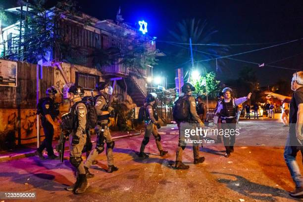 Israeli police officers stand guard in front of a Jewish settler home as local residents broke into brawl, in the Sheikh Jarrah neighborhood in...