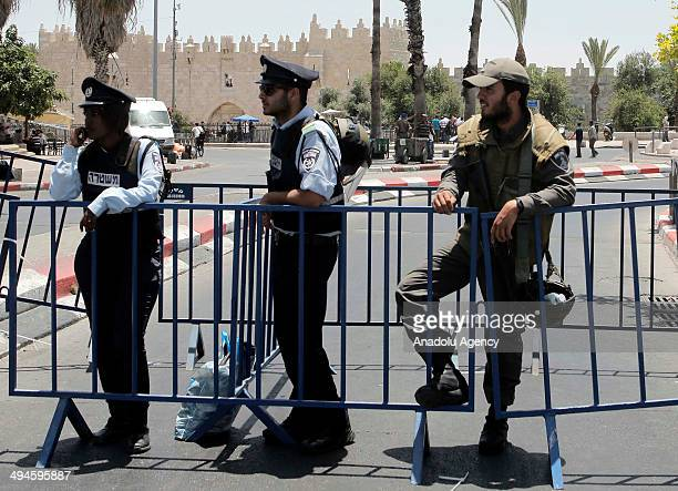 Israeli police officers stand while hundreds of Palestinian youths perform Friday prayers on the streets outside the AlAqsa Mosque compound after...