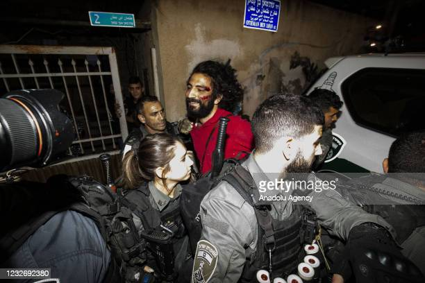 Israeli police officers take a Palestinian into custody during a demonstration at Sheikh Jarrah neighborhood after Israeli government's plan to force...