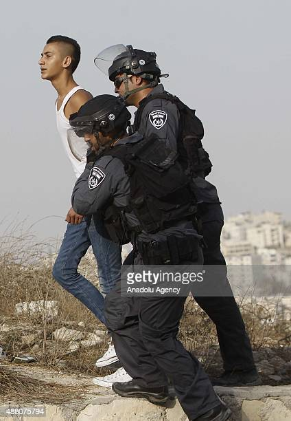 Israeli police officers take a Palestinian protester into custody during the protest against Israeli violations at the AlAqsa Mosque in alIsawiyya...