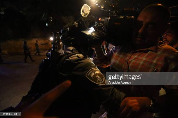 Israeli police officers try to block journalists as they intervene Palestinians with sound bombs and tear gas canisters after clashes erupted between...