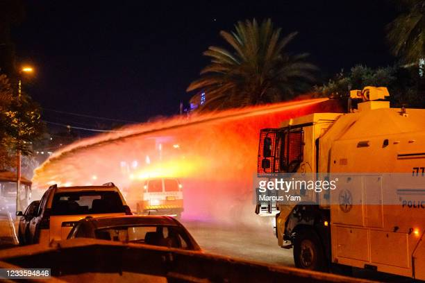 Israeli police officers use a skunk water cannon truck to disperse the crowd that broke into brawl, in the Sheikh Jarrah neighborhood in Jerusalem,...