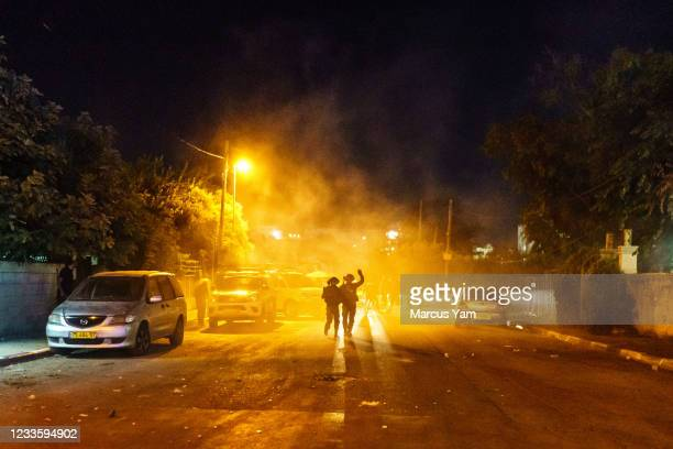 Israeli police officers use tear gas and stun grenades to disperse the crowd that broke into brawl, in the Sheikh Jarrah neighborhood in Jerusalem,...