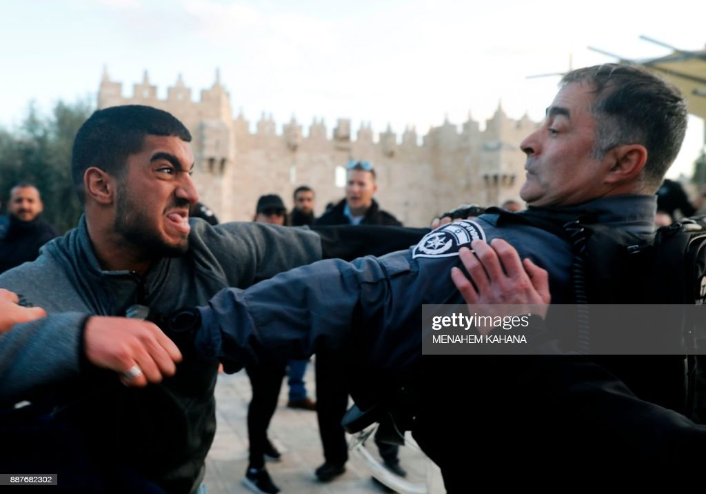 Israeli police scuffle with a Palestinian protestor outside Damascus Gate in Jerusalem's Old City on December 7, 2017. US President Donald Trump's recognition of Jerusalem as Israel's capital sparked a Palestinian general strike and a call for a new intifada as fears grew of fresh bloodshed in the region. / AFP PHOTO / Menahem KAHANA