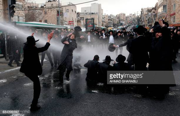 TOPSHOT Israeli police spray water towards ultraOrthodox Jews during a protest against Israeli army conscription in an ultraOrthodox Jewish...