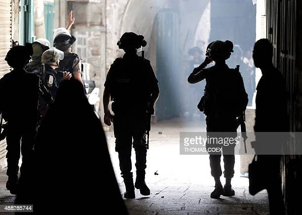Israeli police stand guard after using stun grenades to disperse Palestinian demonstraters in a street of the Muslim quarter in Jerusalem's Old City...