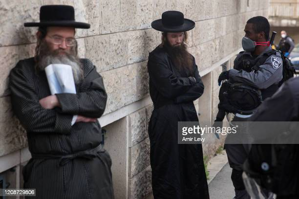 Israeli police troops detain an Ultra Orthodox Jewish man as they enforce a partial Coronavirus lockdown in the Mea Shearim nighborhood on March 31...