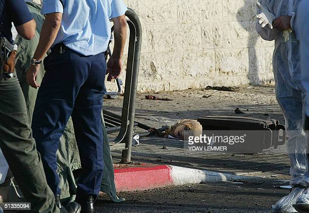 Israeli policemen and forensic experts inspect the scene of a suicide bombing as the head of the female bomber is seen on the ground 22 September...