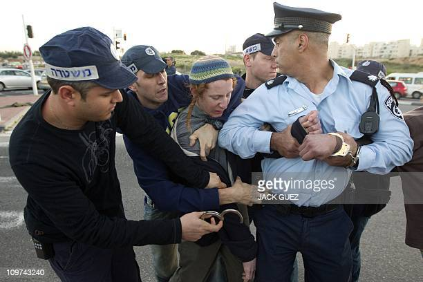 Israeli policemen briefly detain an Israeli settler who was with other protesters blocking a main road at the entrance of Modi'In on March 03 2011...