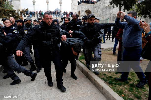 Israeli policemen detain a Palestinian demonstrator during clashes after protesters tried to break the lock on a gate at the Al Aqsa mosque compound...