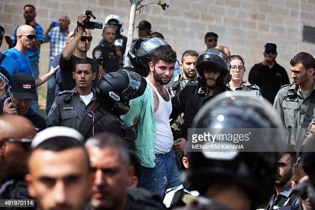 Israeli policemen detain a Palestinian man after stabbing a Jewish teenager in Jerusalem on October 9 2015 An 18yearold Palestinian was arrested...