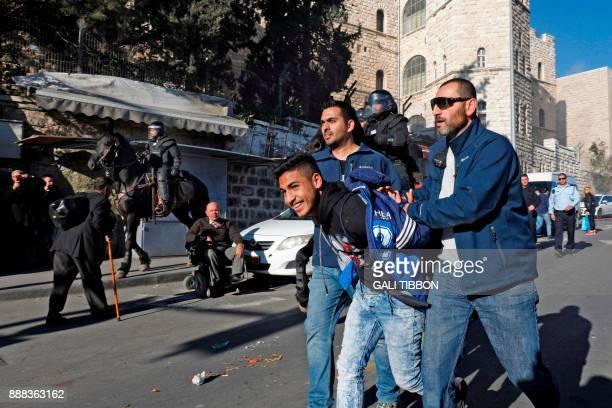 Israeli policemen detain a Palestinian protestor at Damascus Gate in the Jerusalem's Old City on December 8 2017 Palestinians clashed with Israeli...