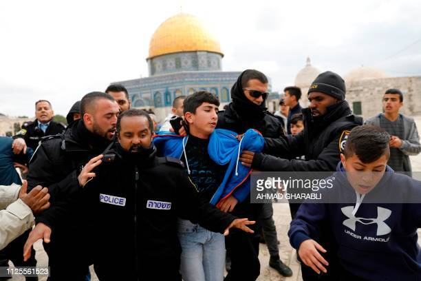 TOPSHOT Israeli policemen detain a young Palestinian demonstrator during clashes after protesters tried to break the lock on a gate at the Al Aqsa...