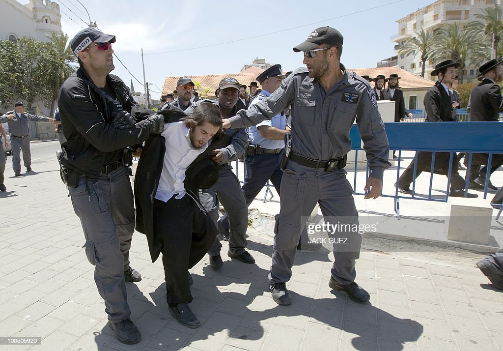 Israeli policemen detain an ultra-Orthodox Jewish man protesting against the removal of ancient tombs in Tel Aviv on May 25, 2010. The remains were exhumed from ancient graves located near the Barzilai hospital in the southern town of Ashkelon last week so that an emergency ward designed to resist rockets can be built to serve residents living near the Hamas-ruled Gaza Strip.