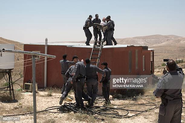 Israeli policemen evacuate a settler from a roof top of the a house in the illegal West Bank settlement of Maale Rehavam southeast of Bethlehem on...