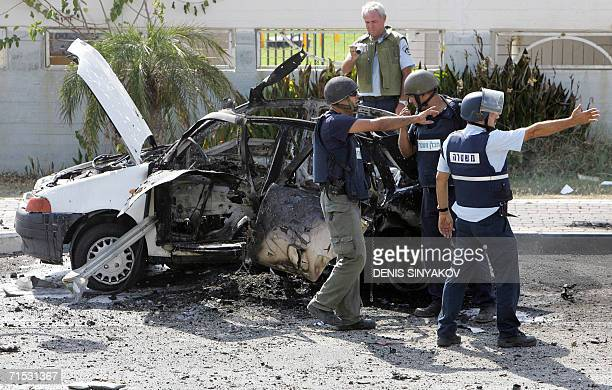 Israeli policemen guard a car damaged by Katyushastyle rocket fired by Hezbollah guerrillas from southern Lebanon in the northern costal Israeli town...