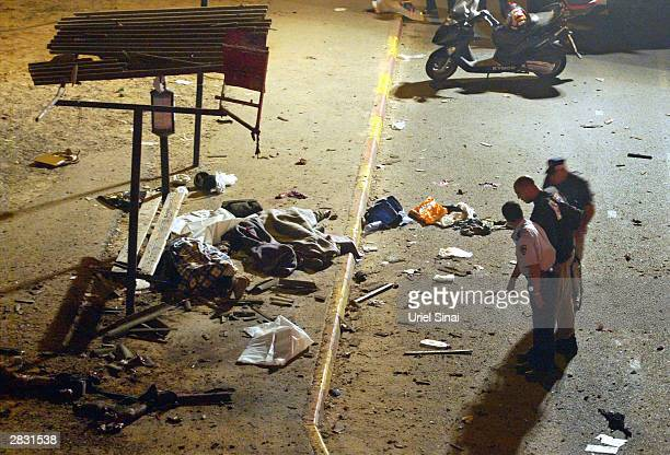 Israeli policemen inspect the scene of a Palestinian suicide attack December 25 2003 at a bus stop in the central Israeli town of Bnei Brak outside...