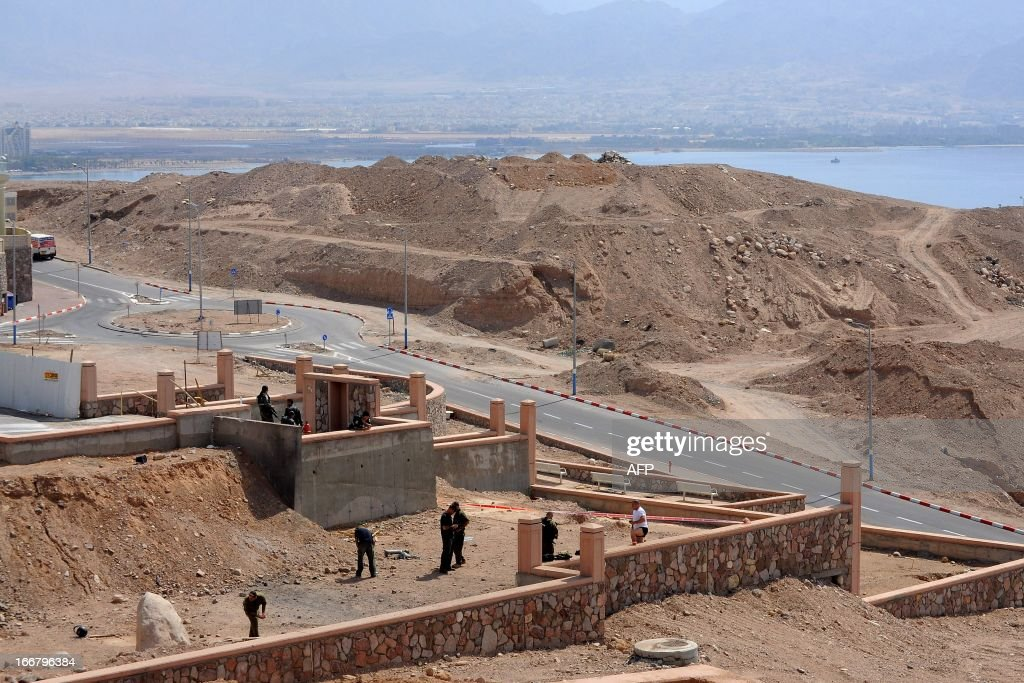 Israeli policemen inspect the site of a rocket explosion in the Israeli Red Sea resort of Eilat April 17 2013. A Salafi jihadist group claimed responsibility for firing what it said were Grad rockets at Eilat, causing no damage or casualties.