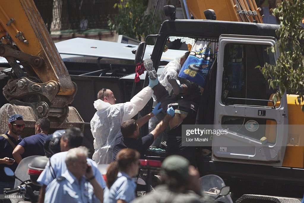 Israeli policemen moves the body of a Palestinian man who was shot by Israeli police officers after he rammed an excavator into a bus on August 04, 2014 in Jerusalem, Israel. The man driving the excavator used the machinery to flip over a bus, killing one. In a seperate incedent, a gunman on a motorcycle opened fire August 4, on a hitchhiking station near Jerusalem's Hebrew University on Mt. Scopus. Several people were wounded in both attacks.
