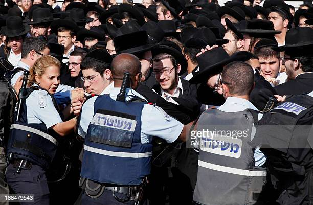 Israeli policemen push back a crowd of Ultra Orthodox Jewish men during the monthly prayer of the liberal Jewish religious group Women of the Wall on...