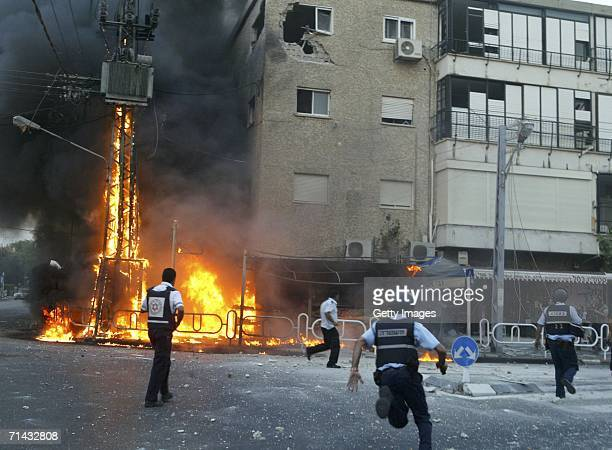 Israeli policemen rush to the scene of a burning electricity pylon and damaged building moments after a volley of Hezbollah Katyusha rockets struck...