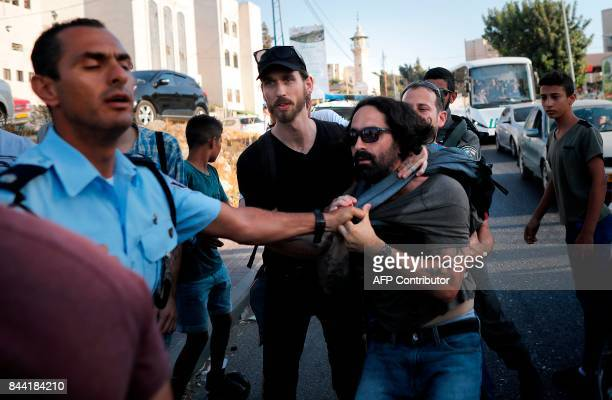 Israeli policemen scuffle with Israeli left wing activists from the Peace Now movement on September 8 during a protest in front of the house seized...