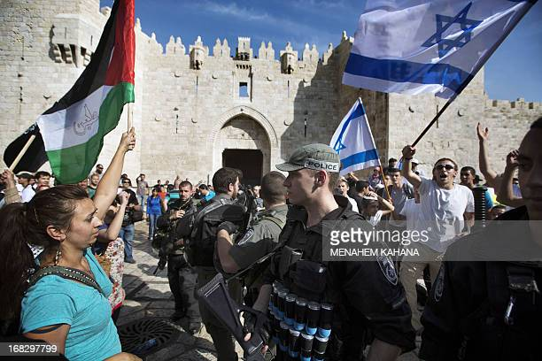 Israeli policemen separate young Israelis holding national flags and Palestinian protestors with their national flags on May 8 2013 in the Damascus...
