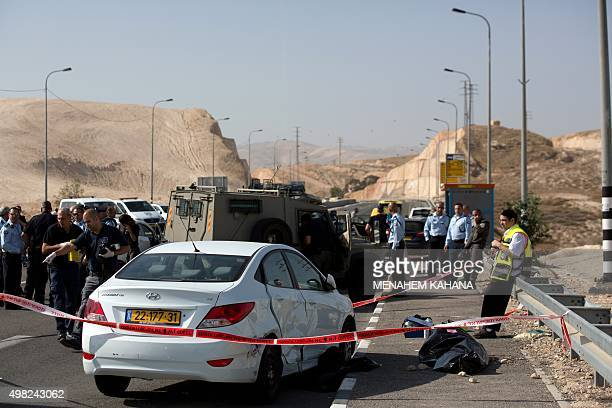 Israeli policemen stand next to a covered body of a Palestinian driver who attempted to ram a taxi he was driving into civilians and charged at them...