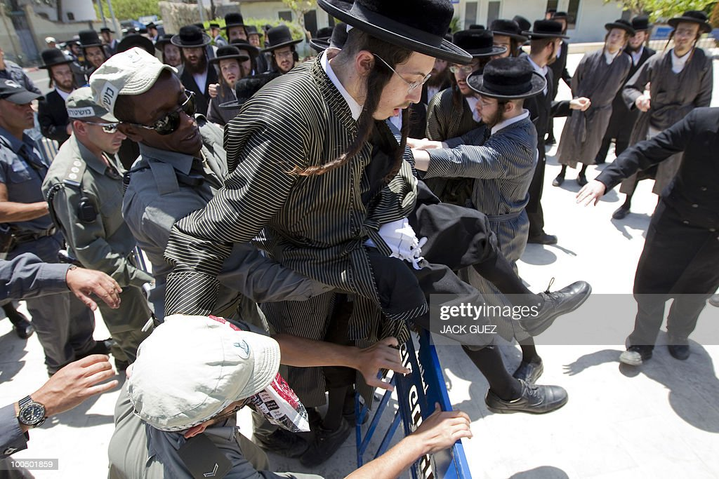 Israeli policemen try to detain an ultra-Orthodox Jewish man during a protest against the removal of ancient tombs in Tel Aviv on May 25, 2010. The remains were exhumed from ancient graves located near the Barzilai hospital in the southern town of Ashkelon last week so that an emergency ward designed to resist rockets can be built to serve residents living near the Hamas-ruled Gaza Strip.