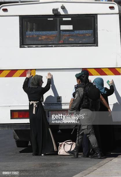 Israeli policewomen frisk Palestinian women next to a vehicle ahead of boarding it to be taken to the West Bank as they stand outside Damascus Gate...