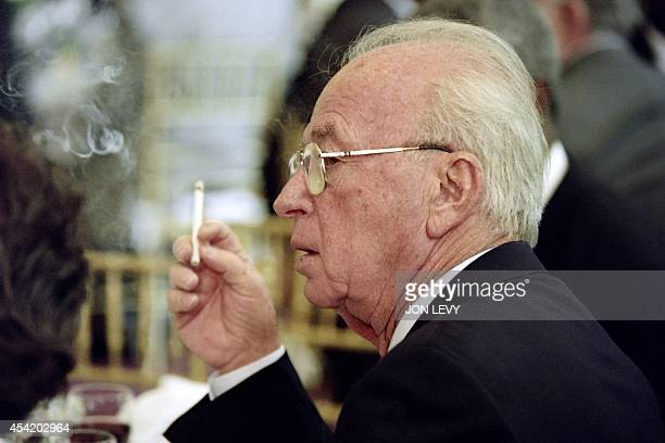 Israeli Premier Yitzhak Rabin smokes on October 24, 1995 during a luncheon hosted by UN Secretary-General Boutros Boutros-Ghali at the United...