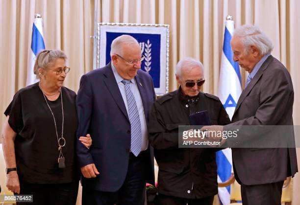 Israeli President Reuven Rivlin and his wife Nehama stand next to French Armenian singer Charles Aznavour as he receives the Raoul Wallenberg medal...