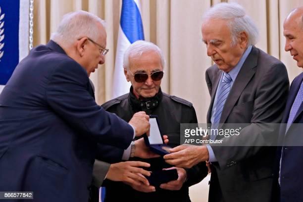 Israeli President Reuven Rivlin presents FrenchArmenian singer Charles Aznavour the Raoul Wallenberg medal on October 26 2017 at the presidential...