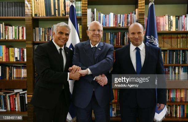 Israeli President Reuven Rivlin shake hands with Prime Minister Naftali Bennett and Alternate Israeli Prime Minister and Foreign Minister Yair Lapid...
