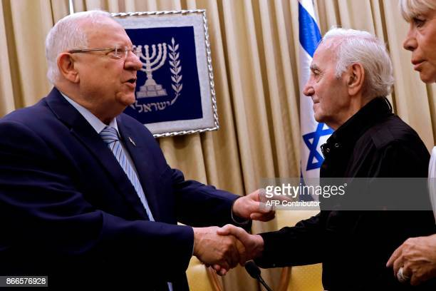 Israeli President Reuven Rivlin shakes hand with FrenchArmenian singer Charles Aznavour on October 26 2017 at the presidential compound in Jerusalem...