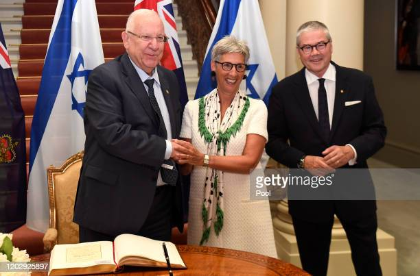 Israeli President Reuven Rivlin shakes hands with as the Governor of Victoria Linda Dessau and her husband Anthony Howard after signing the visitor's...