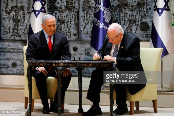 Israeli President Reuven Rivlin signs the letter apppointing Prime Minister Benjamin Netanyahu to form the next government at the former's residence...