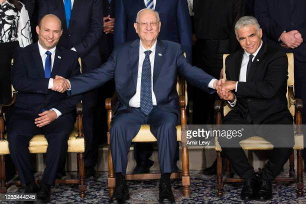 Israeli President Reuven Rivlin sits next to Israeli Prime Minster Naftali Bennett and Foreign Minister Yair Lapid as they pose for a group photo...