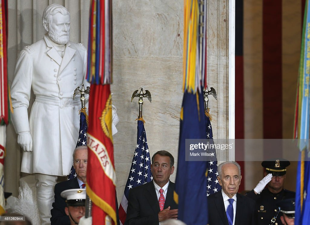 Israeli President Shimon Peres (R), House Speaker John Boehner (R-OH) (C), U.S. Vice President Joseph Biden (L) watch the color guard pass by during a Congressional Gold Medal ceremony at the U.S. Capitol, June 26, 2014 in Washington, DC. President Peres was pressented with the Congressional Gold Medal which recognizes those who have performed an achievement that has an impact on American history and culture.