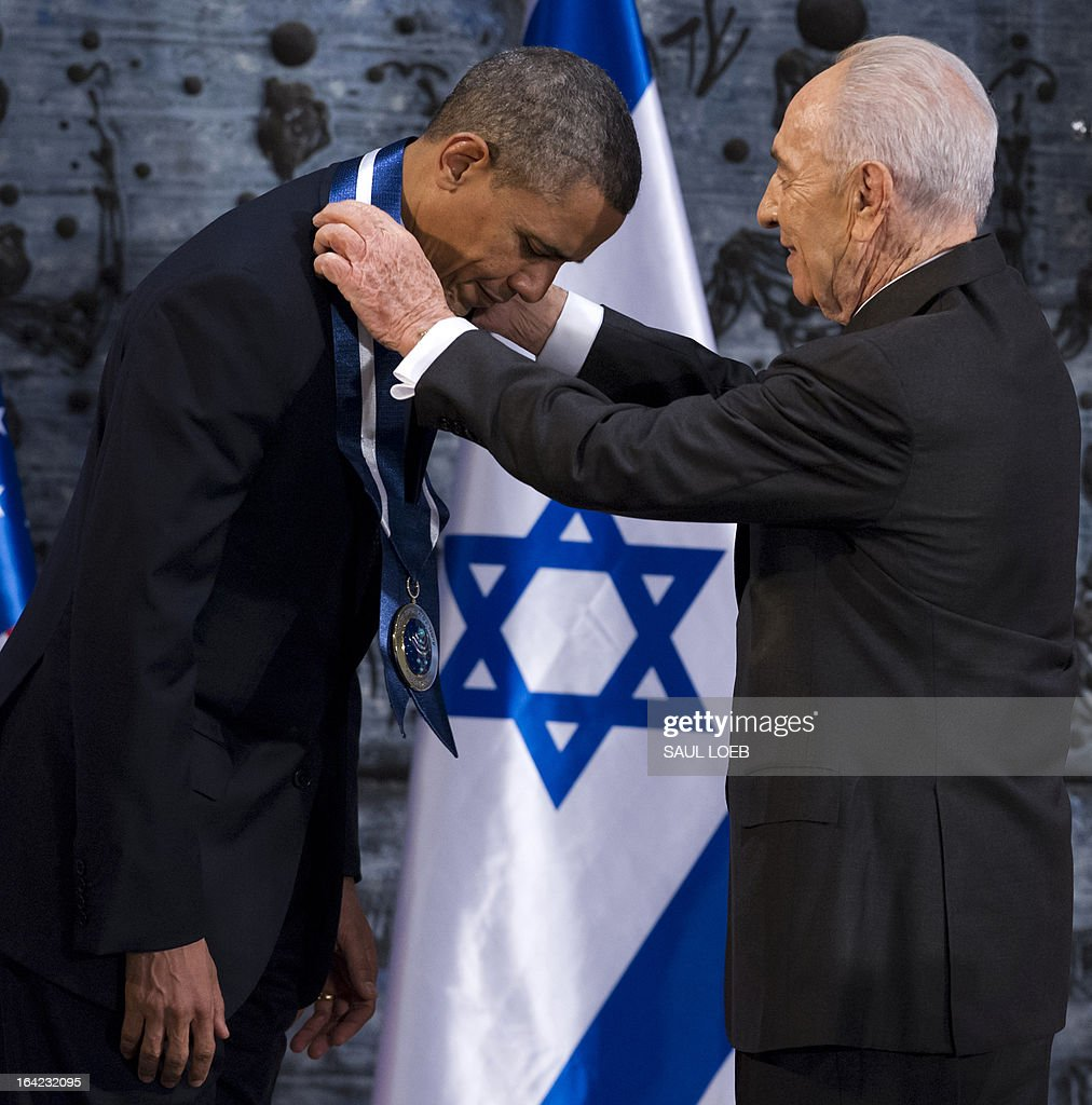 Israeli President Shimon Peres (R) presents US President Barack Obama with the Presidential Medal of Distinction, the highest civilian honor in Israel, during an official State Dinner at the President's residence in Jerusalem, March 21, 2013, on the second day of Obama's 3-day trip to Israel and the Palestinian territories. AFP PHOTO / Saul LOEB