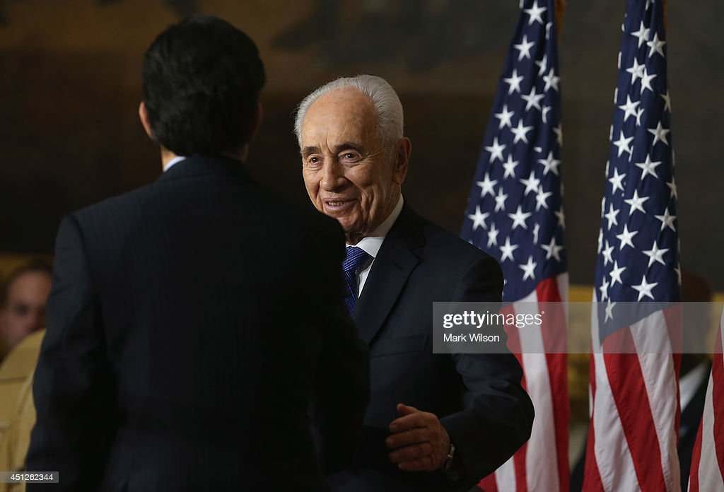 Israeli President Shimon Peres shakes hands with outgoing House Majority Leader Eric Cantor (R-VA) speaks during a Congressional Gold Medal ceremony at the U.S. Capitol, June 26, 2014 in Washington, DC. Israeli President Shimon Peres was presented with the Congressional Gold Medal which recognizes those who have performed an achievement that has an impact on American history and culture.