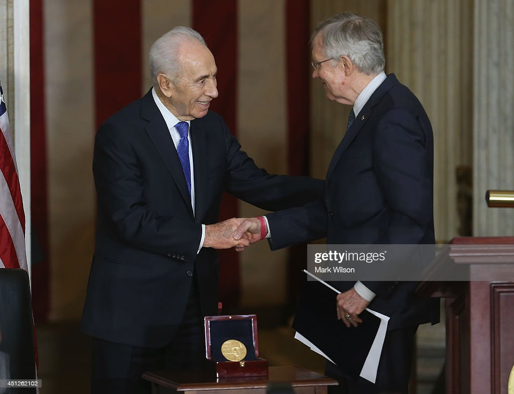 Israeli President Shimon Peres (L) shakes hands with Senate Majority Leader Harry Reid (D-NV) during a Congressional Gold Medal during a ceremony at the U.S. Capitol, June 26, 2014 in Washington, DC. President Peres was presented with the Congressional Gold Medal that recognizes those who have performed an achievement that has an impact on American history and culture. Photo by Mark Wilson/Getty Images)