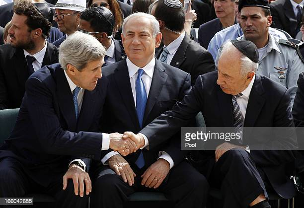 Israeli President Shimon Peres shakes hands with US Secretary of State John Kerry as Prime Minister Benjamin Netanyahu sits in between them during...