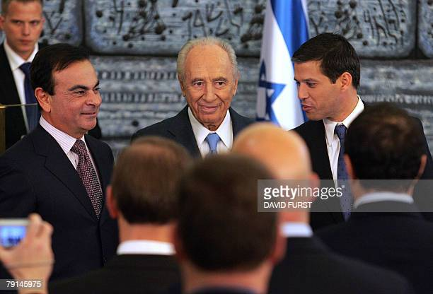 Israeli President Shimon Peres stands alongside President of French automaker RenaultNissan Carlos Ghosn and Director General of Better Place Shai...