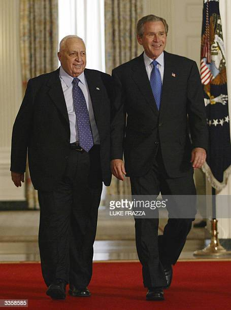 Israeli Prime Minister Ariel Sharon and US President George W Bush walk together to a joint news conference in the Cross Hall of the White House 14...
