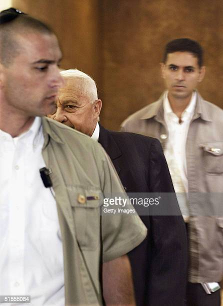 Israeli Prime Minister Ariel Sharon arrives for the weekly cabinet meeting in his Jerusalem offices flanked by two security guards on October 24 2004...