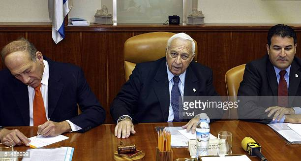 Israeli Prime Minister Ariel Sharon flanked by Deputy Prime Minister Ehud Olmert left and Cabinet Secretary Yisrael Maimon right begins his weekly...