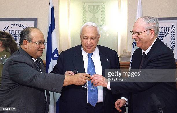 Israeli Prime Minister Ariel Sharon , incoming Mossad chief Meir Dagan and outgoing head Ephraim Halevy join together in a toast October 30, 2002...