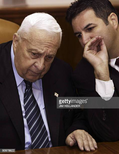 Israeli Prime Minister Ariel Sharon listens to his Cabinet Secretary Israel Maimon as the weekly cabinet meeting gets underway in Sharon's Jerusalem...